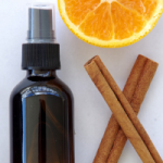 Hand sanitizer spray in an amber glass spray bottle with cinnamon and an orange slice.