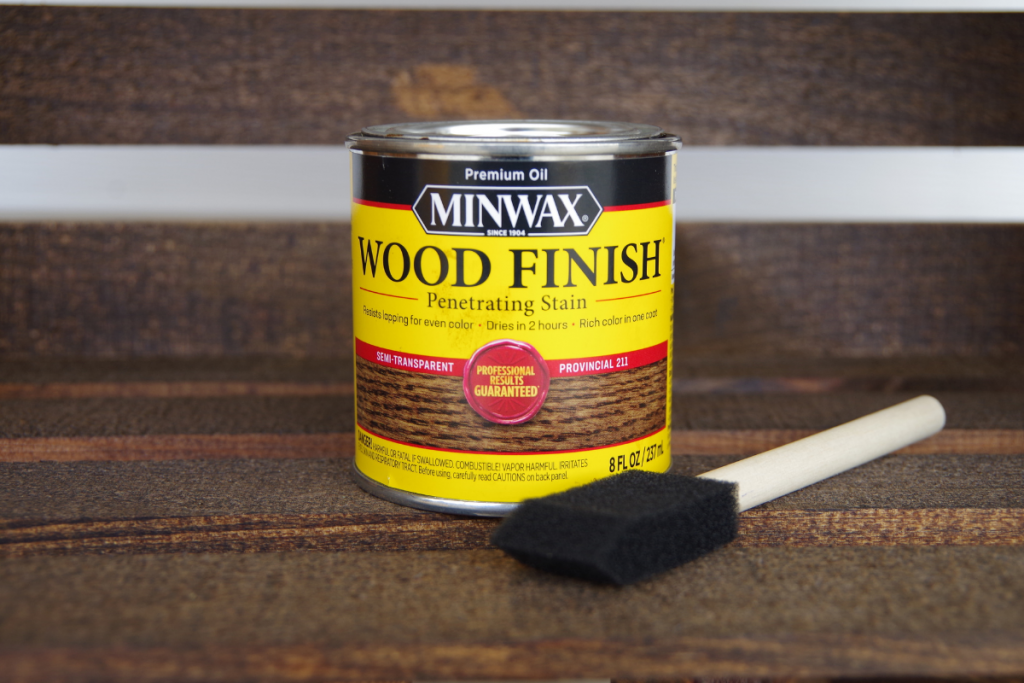 Can of Minwax stain and foam brush used to stain wooden crate bookshelf.